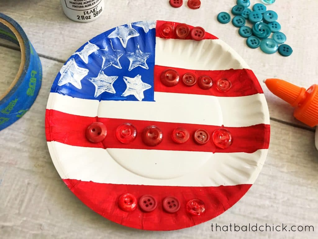 add buttons to red stripes of the paper plate flag
